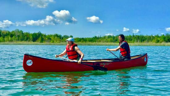 Deux canoéistes qui pagaient sur une étendue d'eau le long d'une rive boisée.
