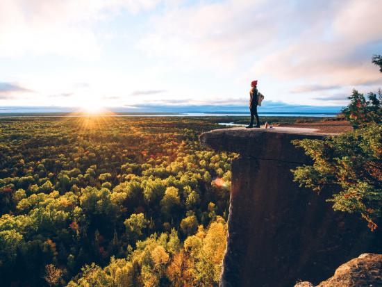 A woman stands on a rock outcropping overlooking a scenic fall colour landscape