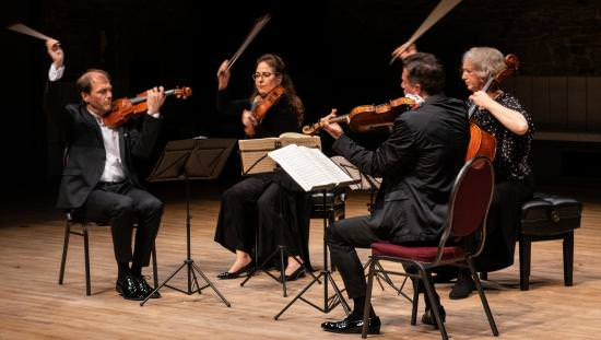 String quartet performing on stage having just played their last note with a flourish