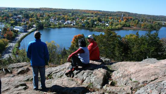 Three visitors standing and sitting on bare rock overlooking Upper Rideau Lake and town of Westport below