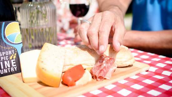 Une personne attrapant de la nourriture dans une assiette de charcuterie