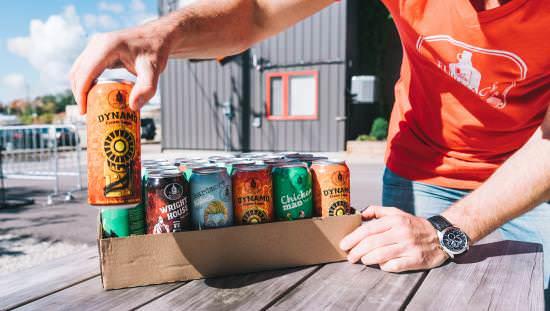 Jeune homme emballant des cannettes de différentes sortes de bières à l'extérieur d'une brasserie.