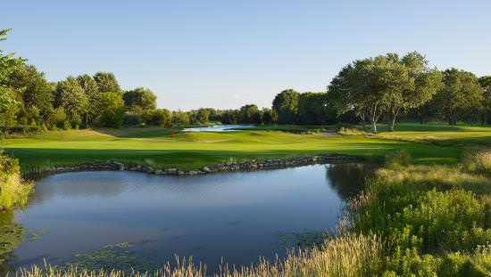 View of golf course fairway from across a lake