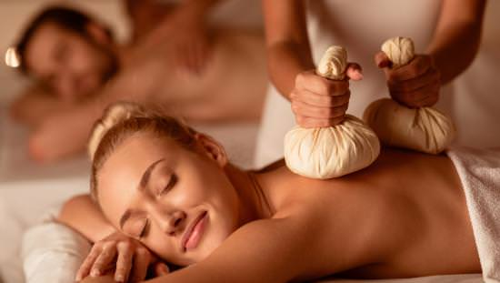 Contented woman lying on massage table with masseuse pressing 2 white cloth bags on her back