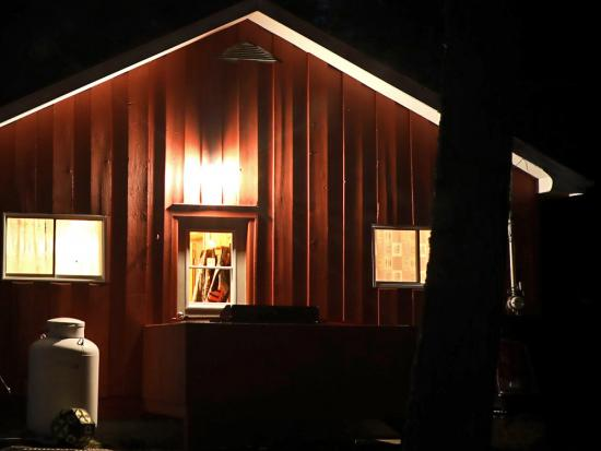 Lights illuminate the side of a rustic, wooden hunting cabin