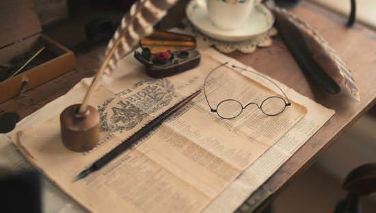 Table avec tasse et soucoupe de porcelaine à côté de la première page d'un journal historique avec des stylos et des lunettes de lecture d'époque sur le dessus.