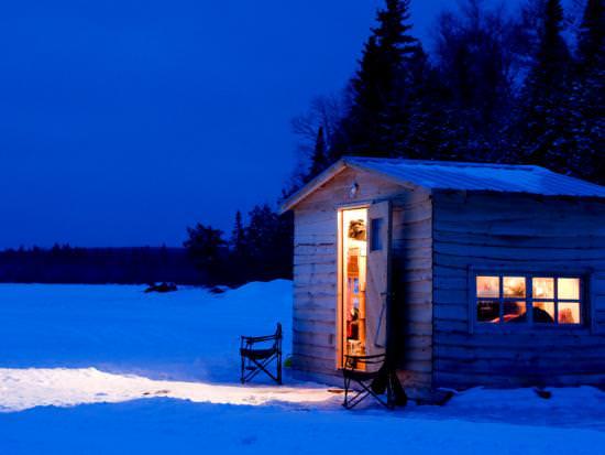 La lumière d'une cabane de pêche sur glace illumine la nuit