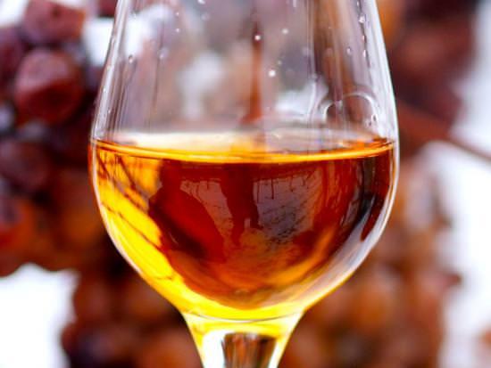 Un verre à vin contenant du vin de glace est tenu devant des raisins congelés sur la vigne
