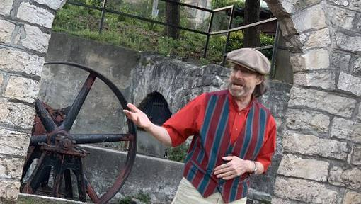 Man standing outdoors in front of old stone mill gesticulating towards something of interest to his right off-camera