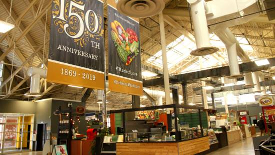 2 banners hanging above extensive array of booths to back wall with one announcing the market's 150th Anniversary