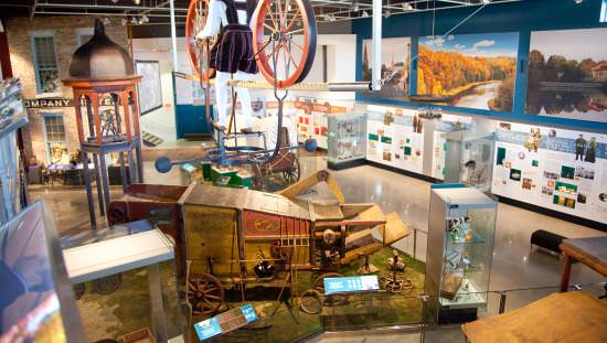 Back of man standing up high between 2 large heritage wagon wheels and surrounded by pioneer furniture and photos on walls