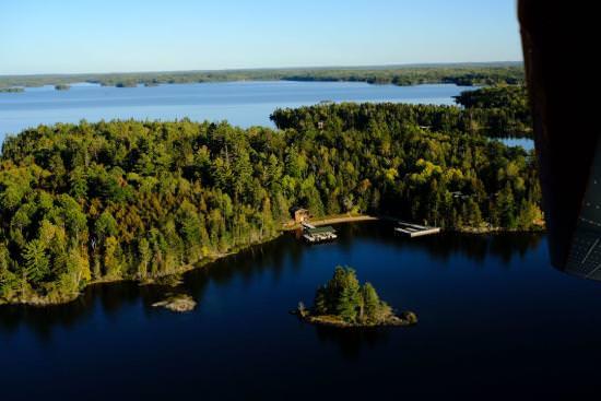 Vue d'en haut sur la nature sauvage épaisse, l'eau pure et un lodge isolé sur le lac des Bois