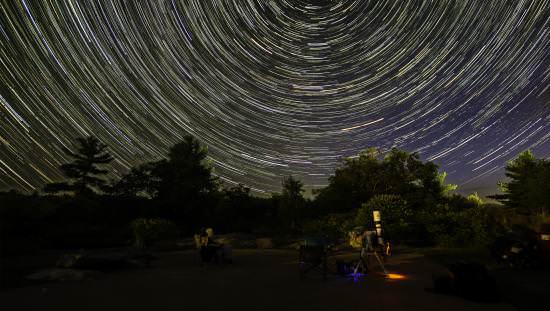 Télescope public face à un bois en arrière-plan submergé d'un ciel de nuit avec des centaines de voies étoilées circulaires, parallèles et brillantes.
