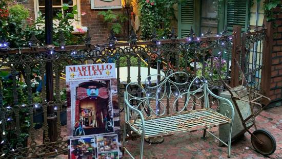Martello Alley poster beside rusty green bench and wheelbarrow on old brick walkway with outdoor café back behind fence