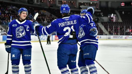 Hockey captain and 2 other players in blue uniforms celebrating on ice with spectators on far side in bleachers