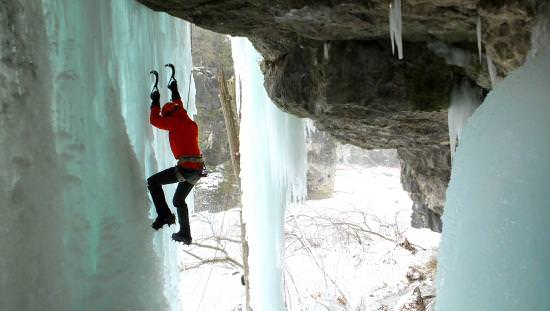 Man just beyond huge rock overhang climbing vertical wall of ice with hands gripping ice with 2 large hooks