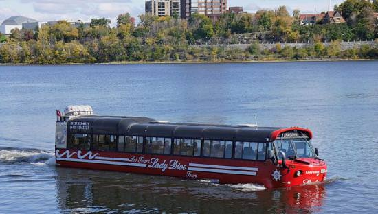 Red Amphibious vehicle floating along in river