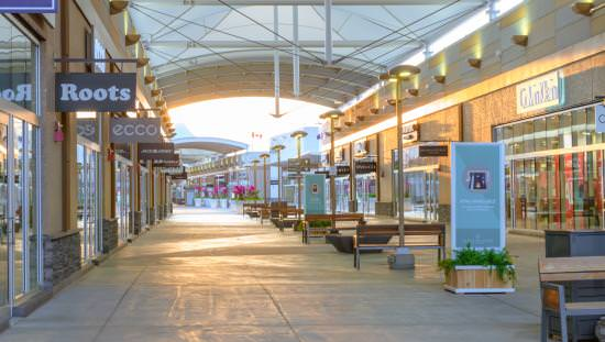 Very long indoor mall with row of benches down middle of aisle and many stores along each side disappearing into the distance