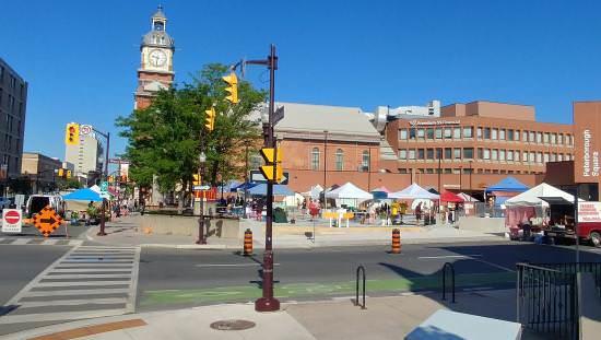 Trottoir du centre-ville avec des gens faisant leurs courses à l'extérieur à des kiosques couverts de toiles de l'autre côté de la rue sur une vaste place centrale et à proximité.