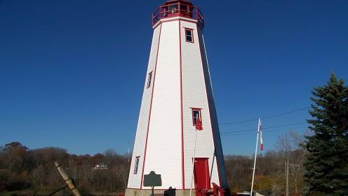 Pelouse verte avec un très grand phare blanc et porte d'entrée rouge ainsi que des marches avant et un balcon avec une forêt plus loin.