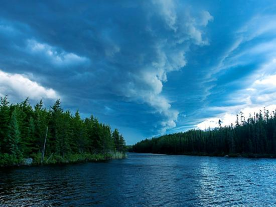 Dramatic cloud formations gather above a peaceful Northern Ontario lake