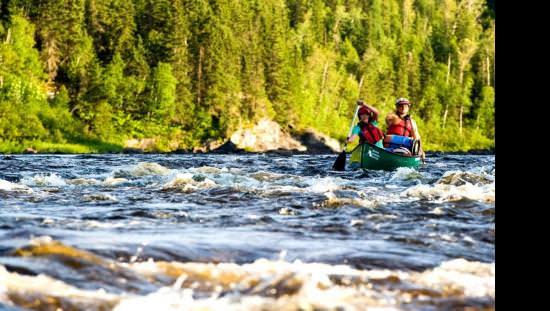 Deux pagayeurs traversent des rapides en canoë dans une rivière sauvage