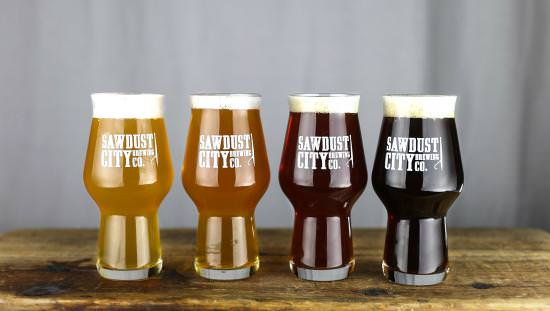 4 glasses each containing an ever darker colour of beer lined up on old wood table and each printed with company name