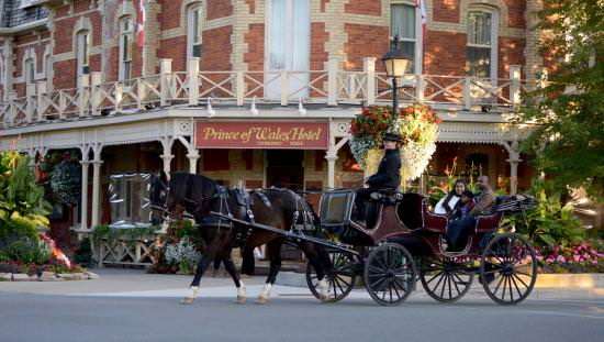 Couple with child in open horse-drawn carriage with driver in heritage-costume passing colourful gardens and heritage hotel