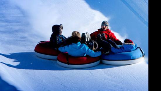 A family of four having fun sliding down a snowtubing run