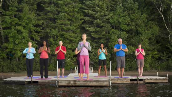Un groupe de personnes pratiquant le yoga sur un quai au bord d'un lac