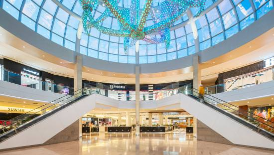 2-storey circular mall with storefronts and lit by many tiny coloured lights on tubes suspended from huge glass dome ceiling