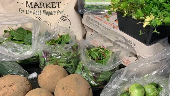 Farmers Market canvas bag on table with 2 cartons of eggs and several potatoes and packages of various green vegetables