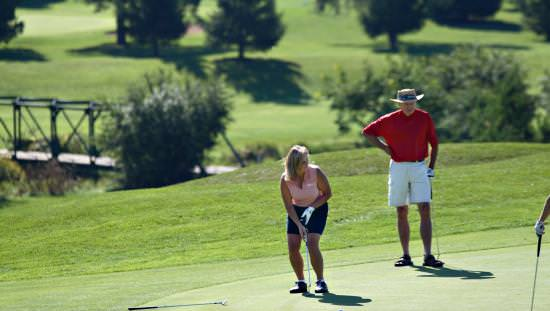 Woman on golf course lining up her golf club for a shot with man standing watching with backdrop of green grass and evergreens