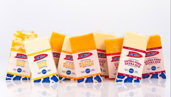 9 labelled packages of alternating orange and yellow cheddar cheese lined up on angles on shiny white reflective tabletop