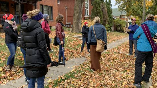 8 people standing on lawn of old house on carpet of autumn leaves and turned towards tour guide who is talking to them