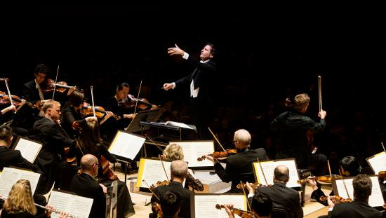 A conductor stands before his orchestra during a performance