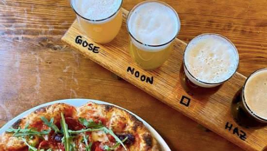 Pizza entière sur une assiette à côté d'un plateau sur lequel se trouve une rangée de quatre verres de bière de différentes couleurs avec le type de bière imprimé sur le plateau.