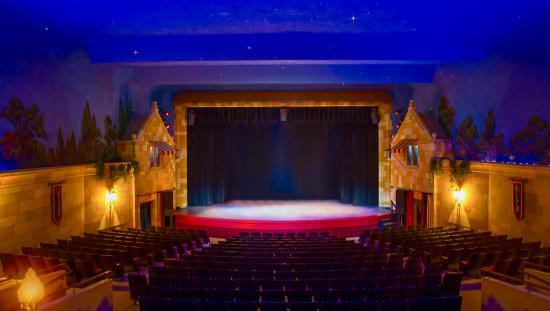 Vue de la rangée arrière d'un théâtre et d'une scène faiblement éclairés