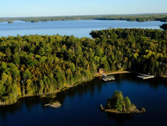 View of the thick wilderness, pristine water and a remote lodge on Lake of the Woods from above
