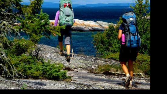 Deux femmes en randonnée le long de la côte du lac Supérieur sur le Sentier transcanadien