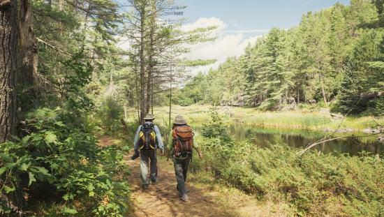 A couple on a hiking trail alongside a lake