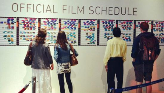 Four people reviewing film schedules on a wall