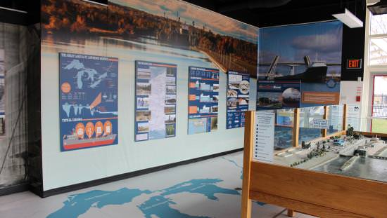 On left wall-size screen of maps and photos and on right large photo of ship in lock above a scale model of lock facility