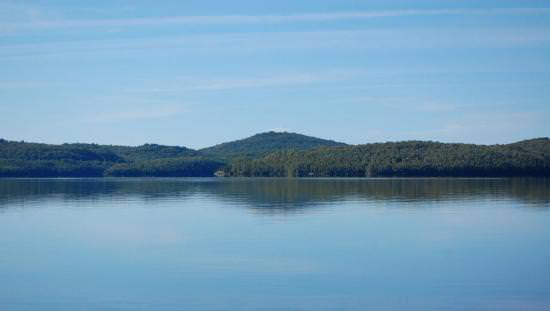 Still blue lake with green forested hills on far side casting soft green reflection in water with deep blue sky above