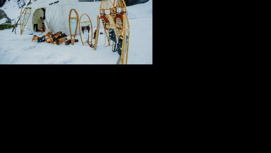 Snowshoes outside of a tent during the winter