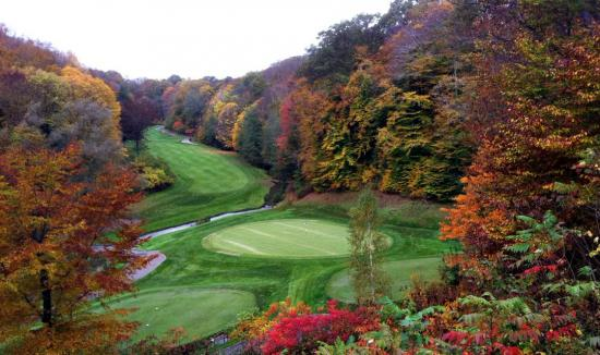 A well manicured golf course surrounded by splendid fall colour