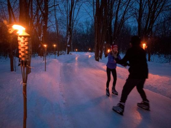 A couple skating on a trail in the evening