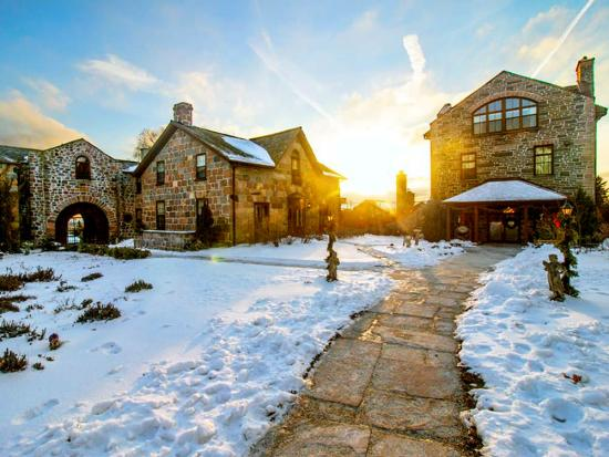 A pathway leads through a snow covered lawn up to old stone buildings