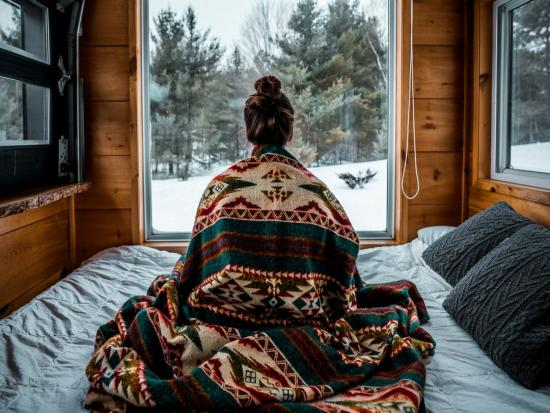 Young girl draped in a blanket and looking out the window