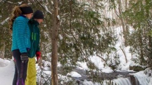 A couple snow shoeing and looking down at the ground